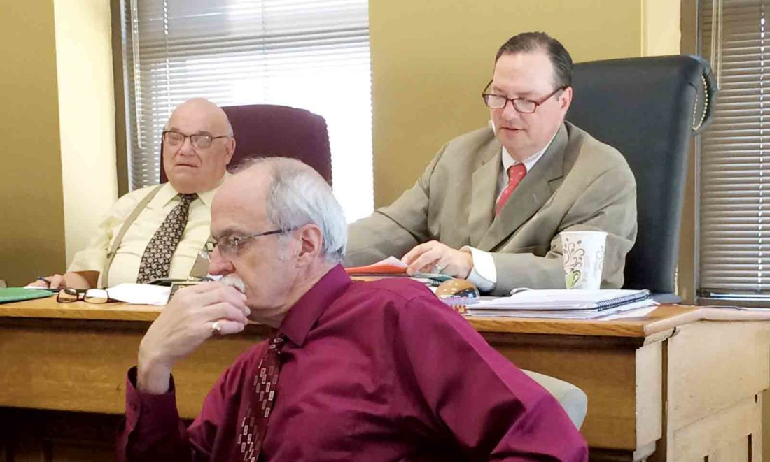 Wood County Commissioners Jimmy Colombo and Blair Couch discuss county employees' insurance coverage with Wood County Administrator Marty Seufer at Monday's commission meeting. (Photo by Brett Dunlap)