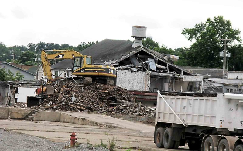 Mounds of construction materials, which have been contaminated by asbestos, are being removed from the former Johns Manville site along River Road. (Photo by Jeffrey Saulton)