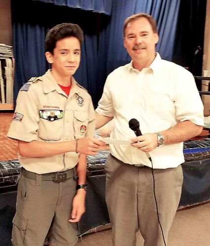 From left, Adem Hupp, 16, of Boy Scout Troop 4 hands $287.58 to Principal Allen Laugh of McKinley Elementary School, the location of Hupp's project to become an Eagle Scout. The money is the remainder of the funds he collected for the project. (Photo Provided)