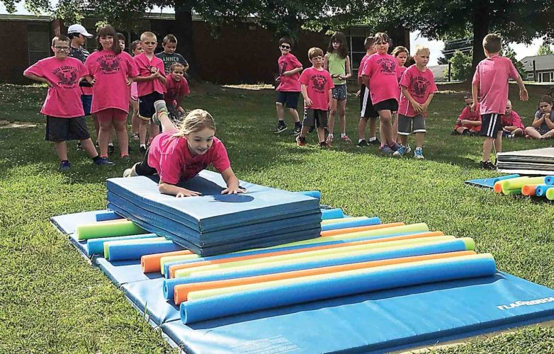 Second-grader Addison Fluharty launches herself on a mat across a row of pool noodles during Friday's Field Day games at Gihon Elementary School. Students spent the last day of school participating in a variety of games and activities. (Photo by Michael Erb)