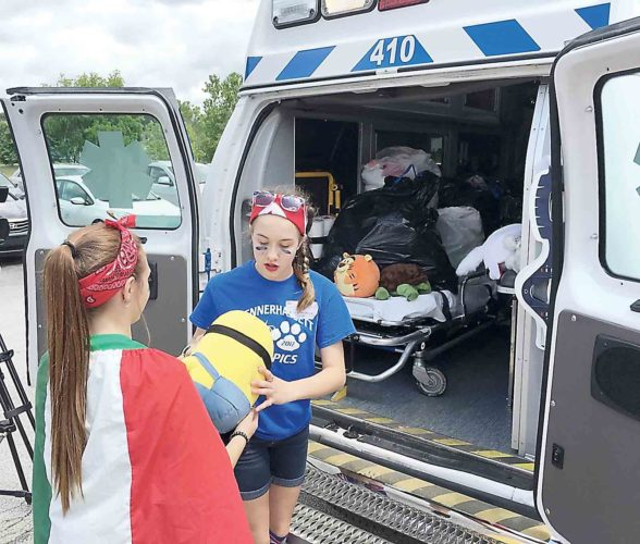 Blennerhassett Middle School eighth-grader Avery Goldsmith, left, hands a stuffed animal to seventh-grader Ainsley Dixon, right, to be loaded into the back of a Camden Clark Medical Center ambulance. The students are members of the STARS club at Blennerhassett, which gathered more than 300 stuffed animals to be given out to young patients and children who are facing a family illness. (Photo by Michael Erb)