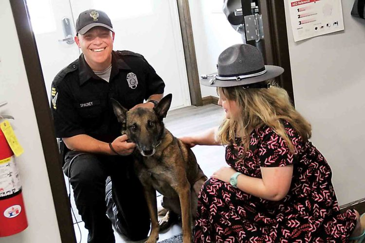 Honorary Trooper Hallie Witte, 9, of Little Hocking, reconnects with Bart and his K-9 handler Trooper Brian Stackey Friday at the Marietta Post of the Ohio State Highway Patrol. (Photo by Janelle Patterson)