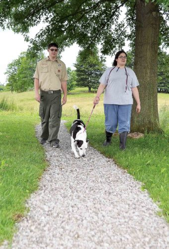 Devin Aufdenkampe walks with Devon Stout, canine kennel tech, and Sparky, a 5-year-old lab mix, on Thursday. Aufdenkampe recently constructed the walkway at the Humane Society of the Ohio Valley as an Eagle Scout project. (Photo by Kate York)