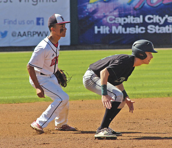 Ravenswood shortstop Nic Taylor shadows Charleston Catholic's Trae Swisher at second base in preparation of a pick-off attempt during the Irish's 8-2 Class A state championship game win over the Red Devils Saturday at Appalachian Power Park in Charleston. Photo by Joe Albright.