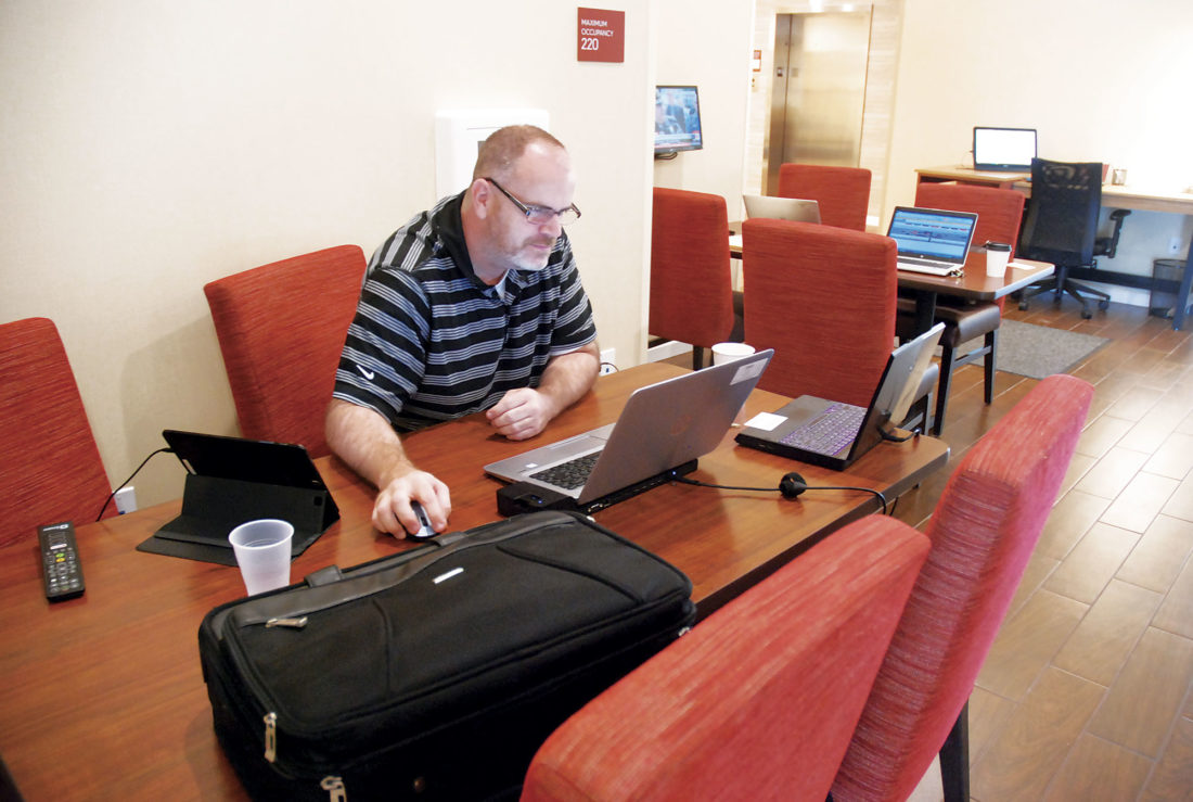 Photo by Evan Bevins Christopher Morrow, lead analyst with the Federal Reserve Bank of St. Louis, takes advantage of the Internet access at the TownePlace Suites by Marriott on Seventh Street in Parkersburg Wednesday. Morrow is lodging at the recently opened extended-stay facility while in town for business at the Bureau of the Fiscal Service.