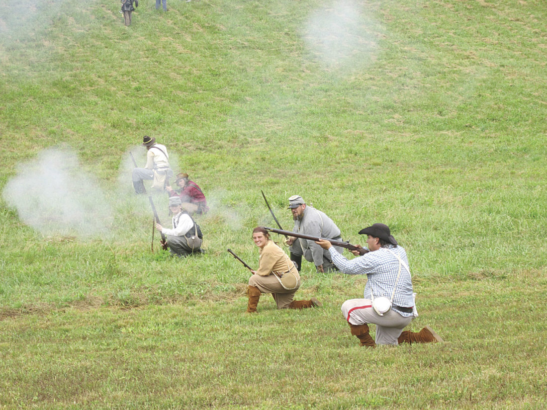 Photo by Wayne Towner Confederate soldiers fire at the Union line Sunday during the annual Civil War Re-enactment Weekend at Henderson Hall at Boaz. Re-enactors set up period camps at the historic home and presented a simulated battle on Saturday and Sunday afternoons.