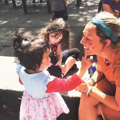 Photo Provided Breckin Wells, 22, of Vienna and a girl, 2, paint each other's faces in a park in Queens, New York.