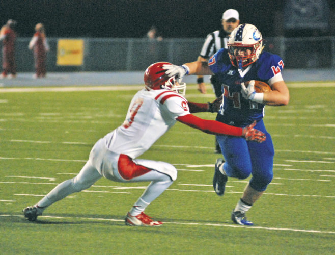 Gilmer County's Cole Haley, pictured here giving a stiff arm to Calhoun County's Caden Hicks, will continue his career on the gridiron at Concord University. Photo by Joe Albright.