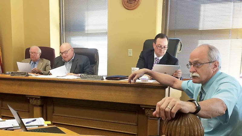Wood County Commissioners, from left, Bob Tebay, Jimmy Colombo and Blair Couch reviewed bids for infrastructure projects at the Emerson Commons tax increment financing (TIF) district during Monday's meeting as County Administrator Marty Seufer answered procedural questions and concerns. (Photo by Brett Dunlap)
