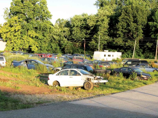 Several cars are still left to be removed from the Alliance Auto Center property in Williamstown. In an agreement with the city signed May 16, the lot was to be cleared of cars by July 1. (Photo by Jeffrey Saulton)
