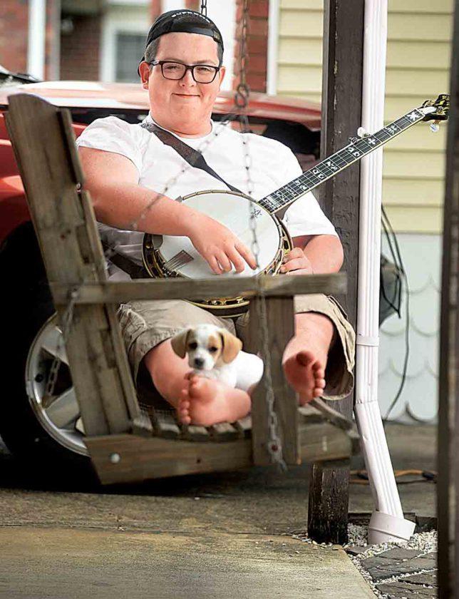 Photo by Jeff Baughan Jake Eddy sits in a swing with his pup Wally at his grandmother's home in Parkersburg.