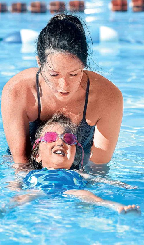 Taylor Foster helps Gabby Schall float on her back during beginning swimming lessons at North Hills Pool. (Photo by Jeff Baughan)