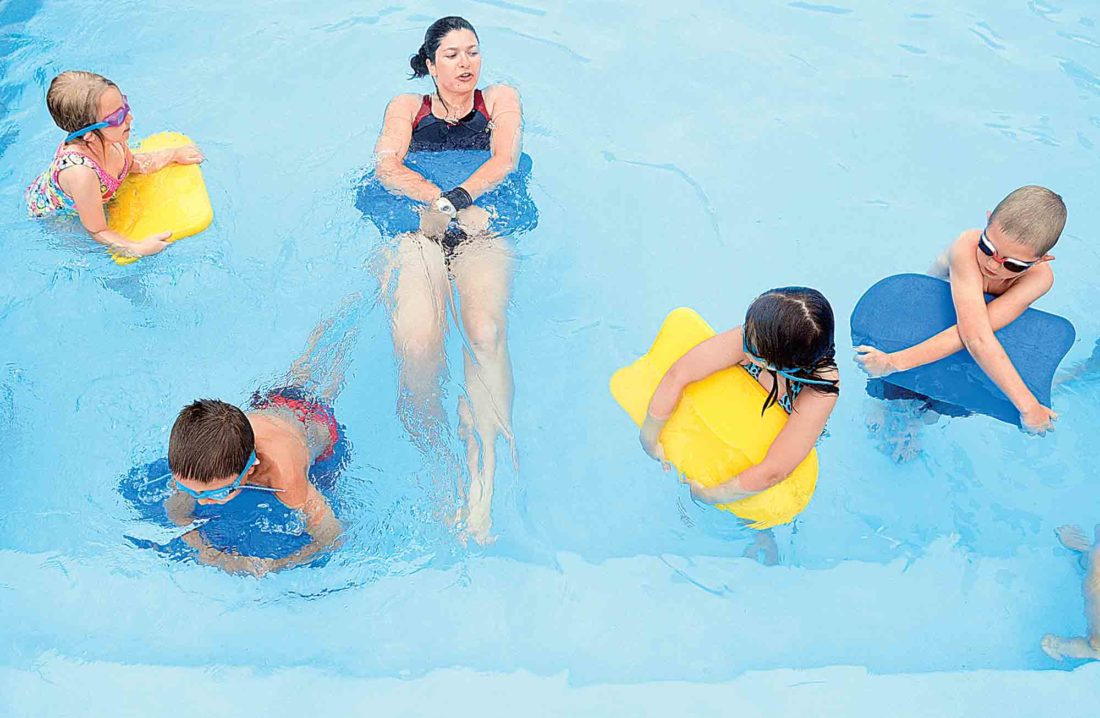 Instructor Analisa Vann kicks away from the side of the pool doing a backfloat as students move against the wall. (Photo by Jeff Baughan)