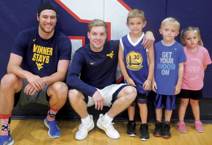 Photo by Steve Hemmelgarn WVU basketball players (from left) Nathan Adrian and James Long pose with Trey, Trevor and Raegan Myer before a youth clinic Wednesday at Parkersburg South.