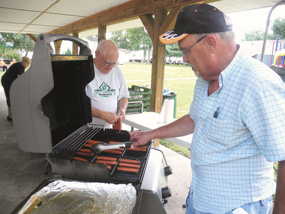Photo by Jeffrey Saulton Belpre Mayor Mike Lawrentz, right, grills hot dogs with Larry Nutter, left, at the annual Belpre High School Alumni Association ice cream social at Howes Grove Park Saturday.