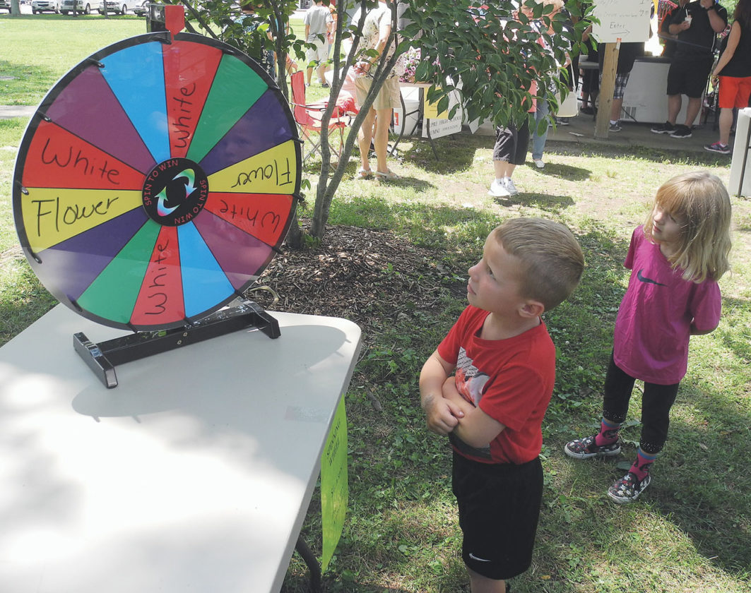 Photo by Jeffrey Saulton Mason Henthorne spins a wheel for a prize as Maggie Menefee watches.