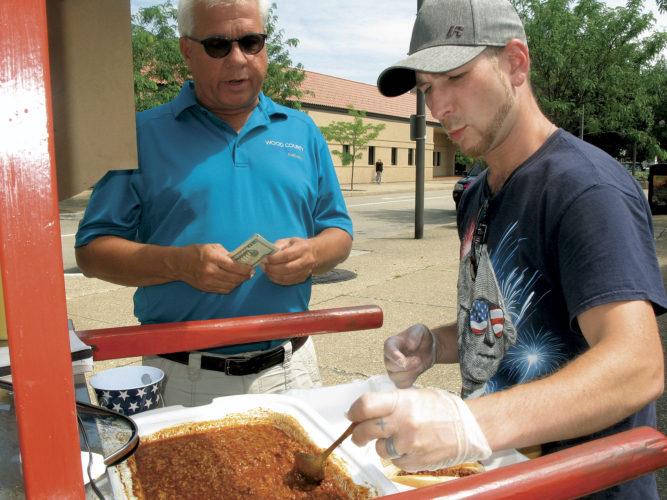 Photo by Jess Mancini Solid Waste Authority director John Reed, left, waits for two hot dogs with sauce from Will Heflin of Hot Dog Willy's, a hot dog stand by Bicentennial Park at the courthouse. Reed likes the homemade sauce.