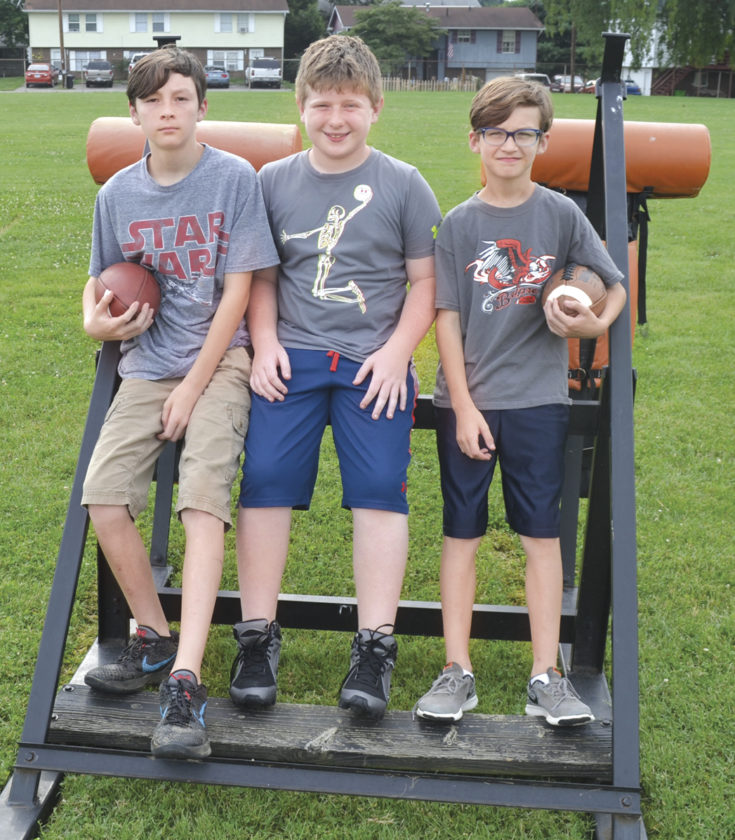 Belpre Youth Football players, left to right, Braden Green, Willis Starcher, and Thomas Green, pose for a photo at the Belpre High School practice field Tuesday. Photo by Ron Johnston.