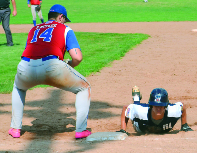 Photo by Ron Johnston Marietta Post 64's Trent Dawson, right, dives back to first base as Cambridge Post 84's Steve McPeek fields a pickoff throw during an American Legion Region 8, District 11 tournament baseball game Friday at Don Coss Field in Cambridge.