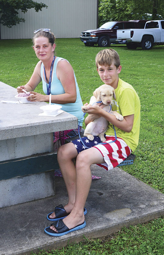 Photo by Doug Loyer Hannah Ball, Dylan Ball and puppy Ratchet enjoy eating ice cream at the social.