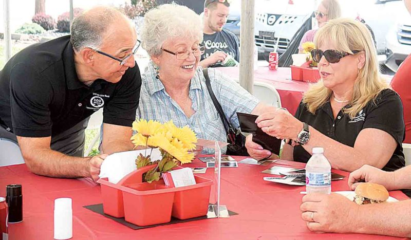 Financial consultant Paul Mancuso, left, former Community Bank employee Connie Anderson and lender Mary Barnette look over pictures of the Community Bank at Monday's luncheon. (Photo by Jeff Baughan)