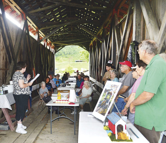 Photo by Doug Loyer Deb Root Shell, holding paper, gives a presentation about the Root Covered Bridge before the unveiling of the historic marker.
