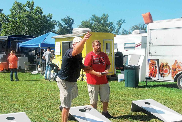 File Photo Dave Rose, left, tosses a cornhole bag in last year's Wirt County Fair Cornhole Tournament on Saturday as Ron Steele looks on. The 2017 Wirt County Fair runs Aug. 2-5 at Camp Barbe in Wirt County.