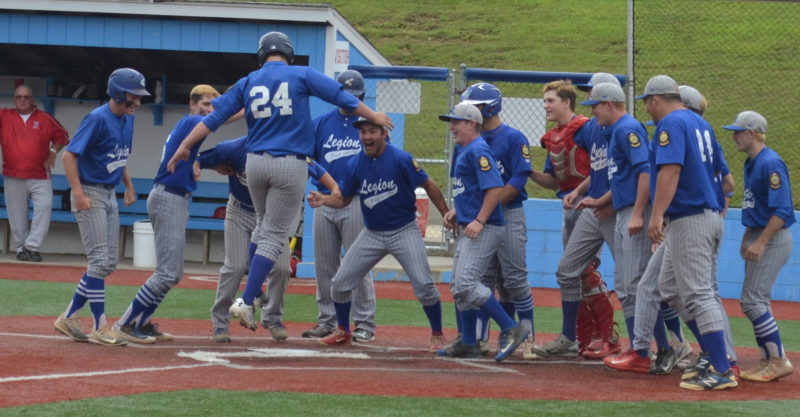Photo by Ron Johnston Beverly/Lowell's Tyler Bradford (24) is greeted at home plate by his teammates after slugging a two-run blast in the first inning Friday at Beavers Field in Lancaster. BevLow beat Sidney, 7-4, to advance to another winner's bracket game this morning.
