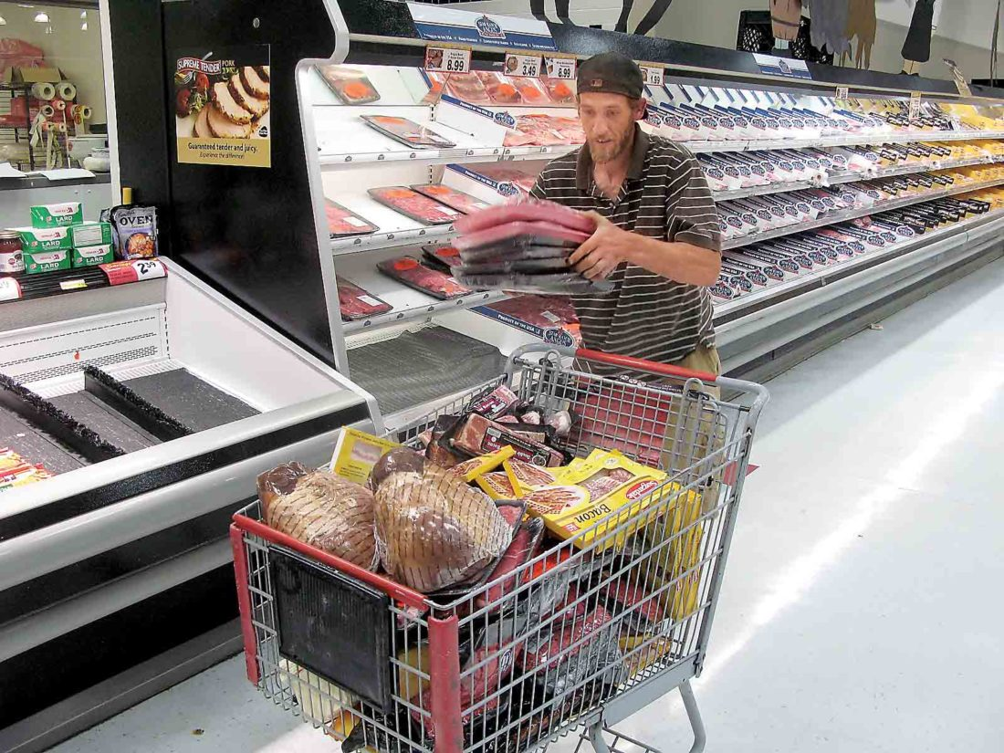 Photo By Jess Mancini Todd Trudo, designated runner for his mother Debbie Trudo of Little Hocking dumps steaks, chops, chicken and seafood into a cart during the Supermarket Sweepstakes sponsored by Foodland and The Parkersburg News and Sentinel.