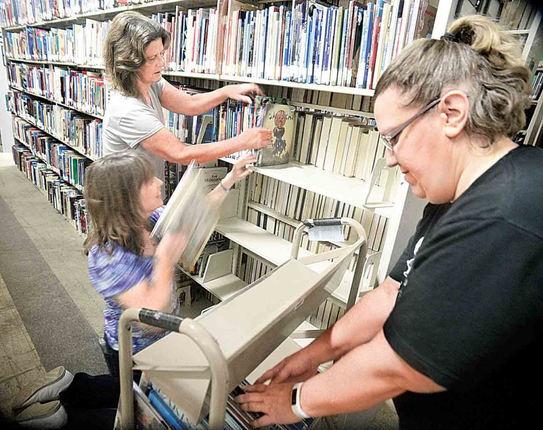 Photo by Jeff Baughan While Teresa Wilkinson, right, moves books on a cart, Janet Mongilio, center, stacks the books on a shelf and Marcia Durnell holds shelved books in place Friday.