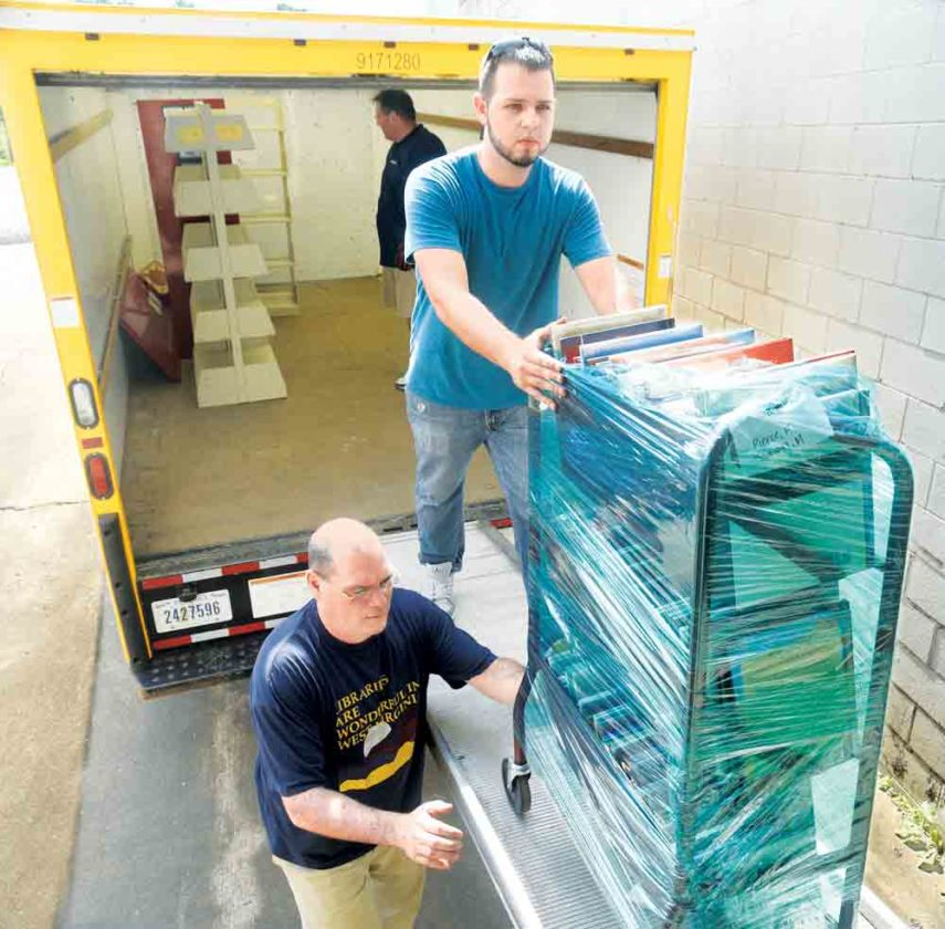 Photo by Jeff Baughan Parkersburg and Wood County Public Library Executive Director Brian Raitz, bottom, helps Zach Claypool of Select Office Services move books into a warehouse Friday while Shane Bennett readies more items in the moving truck.