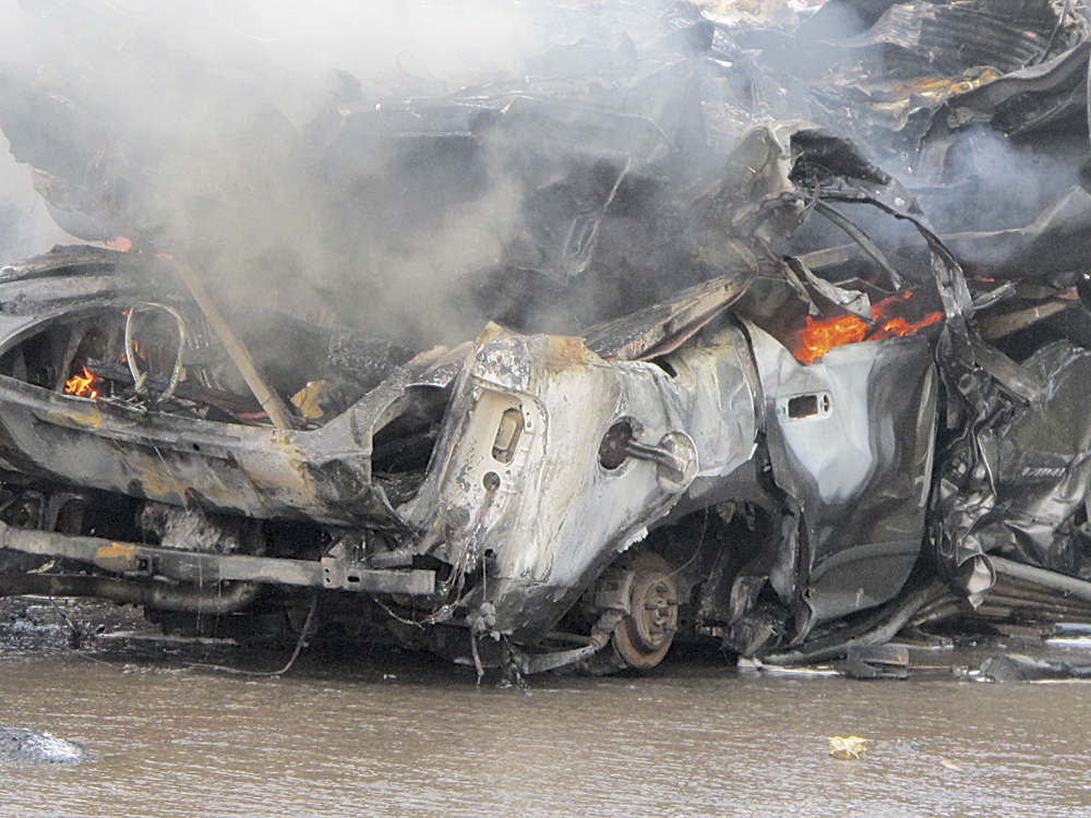 Photo by Jess Mancini Cars burn Saturday afternoon in a car being scrapped at RJ Recycling on Garfield Avenue. The Parkersburg Fire Department sent its arsenal of equipment to the fire which was caused when a battery exploded during the recycling process.