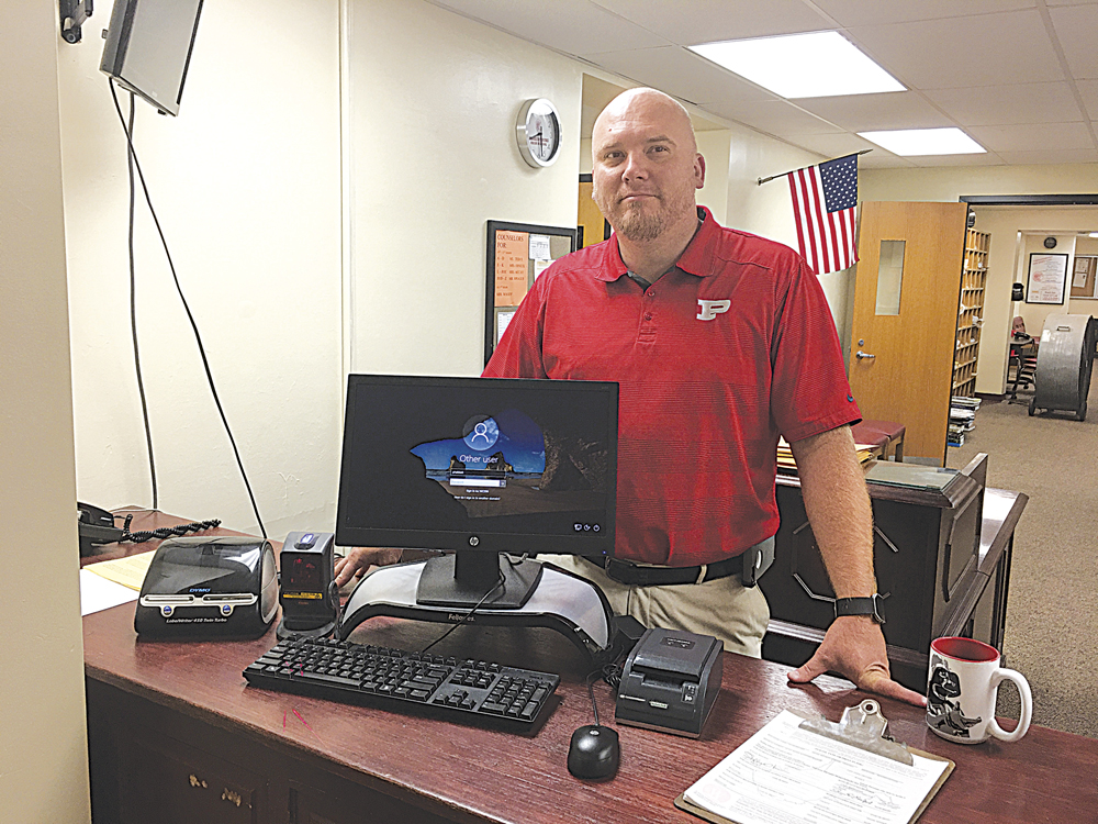 Photo by Michael Erb Parkersburg High School Principal Kenny DeMoss stands next to one of the four Hall Pass Visitor Management System computers which will track student tardiness as well as school visitors for the 2017-18 school year.