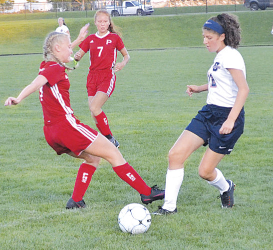 Parkersburg South's Samantha Martin, right, dribbles by Parkersburg High's Jordan Balog, left, during girls soccer action Friday night at the Erickson All-Sports Facility. South won 5-1. Photo by Ron Johnston.