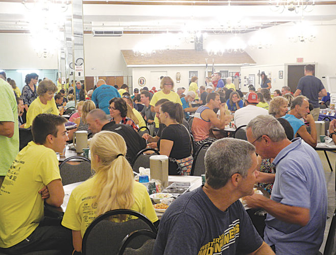 Participants of the half marathon enjoy pasta at the St. Xavier Parish Center Friday evening before this morning's race. Photo by Steve Hemmelgarn.
