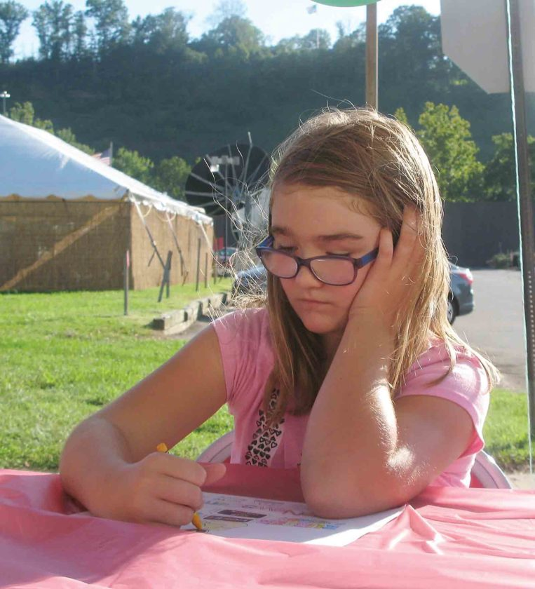 Photo by Jeffrey Saulton Isabella Howard, of Parkersburg, works on an entry for the Homecoming coloring contest during the opening of the Parkersburg Homecoming Friday evening.