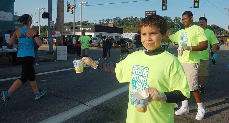 File Photo From left, Devon Martin, Melvin Stubbs and Rob Graham hand out water at the Washington Works water stop during a past News and Sentinel Half Marathon.