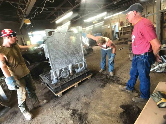 Photo by Janelle Patterson Brad Smith, right, looks over an aluminum marker for West Virginia after men in his foundry remove the sand Wednesday.