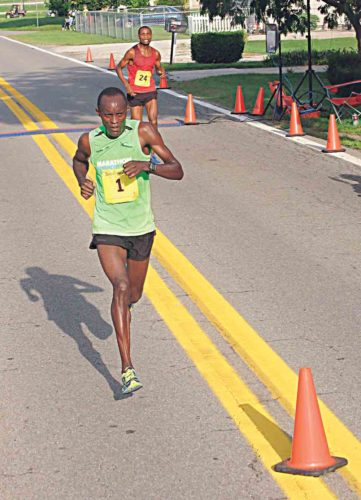Photo by Jay W. Bennett Julius Kogo races in the News and Sentinel Half Marathon Saturday in Parkersburg. Kogo won his seventh race in eight years with a winning time of 1:03.09.