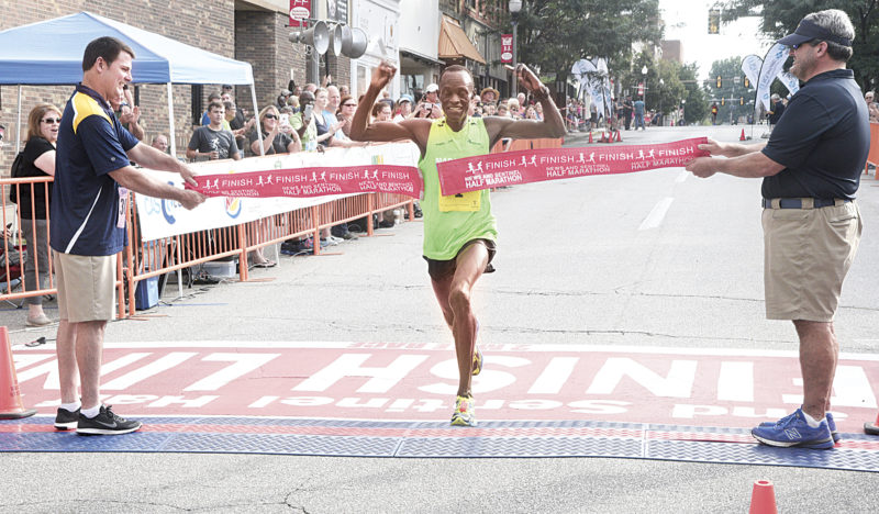 Photo by Jeff Baughan Julius Kogo breaks the tape during the 31st running of The News and Sentinel Half Marathon Saturday in Parkersburg. Kogo won his seventh race in eight years with a winning time of 1:03.09.