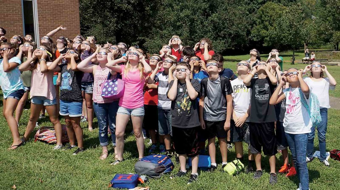 Sixth-grade students at Belpre Elementary School gather outside to view the 2017 solar eclipse while using special protective eyewear. Belpre City Schools extended the school day by 20 minutes Monday to give students and staff the chance to safely witness the celestial event. (Photo by Michael Erb)