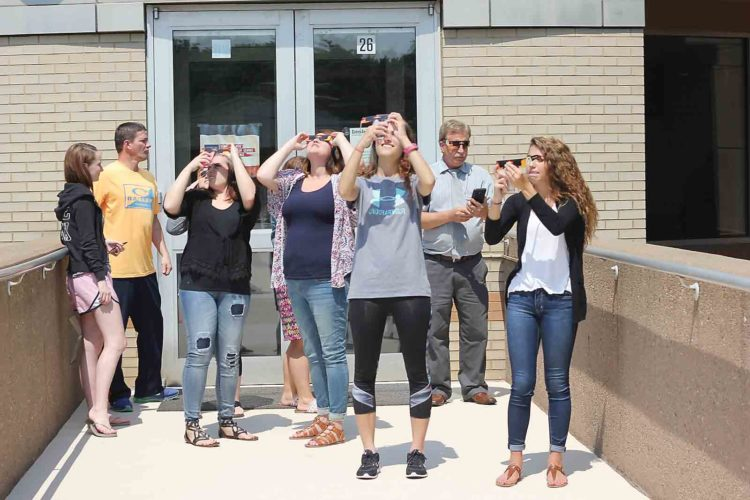 Students stop to take photos of the solar eclipse through viewing glasses Monday at Washington State Community College. (Photo by Janelle Patterson)