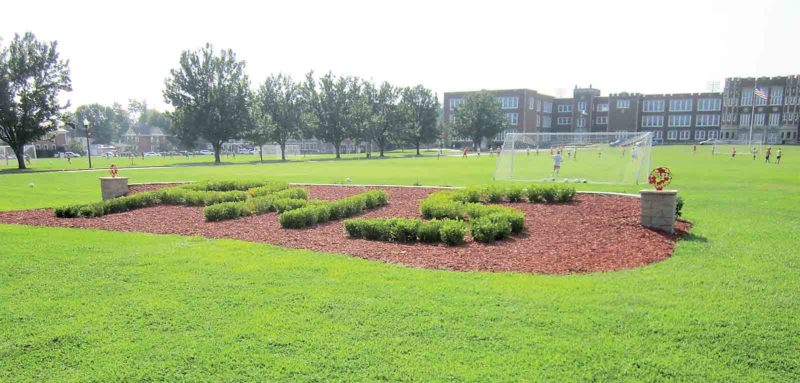 Bushes spelling out PHS, roses and metal Indian heads on columns are part of the new landscaping in front of Parkersburg High School. (Photo by Wayne Towner)