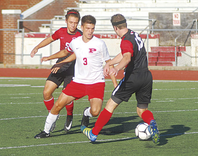 Parkersburg senior Parker Miller fights for control of the ball against Bridgeport's Tyler Whiteman (5) and Broc Oliverio (16) during Wednesday's match at Stadium Field. The Big Reds and Indians played to a 2-2 tie. Photo by Jay W. Bennett.