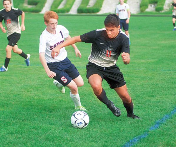 Photo by Jay W. Bennett Parkersburg South's Cameron Frame tries to keep pace with University's Joseph Biafora during Thursday's soccer match at the Erickson All-Sports Facility. Biafora tied a career high with four goals during the Hawks' 6-0 triumph.