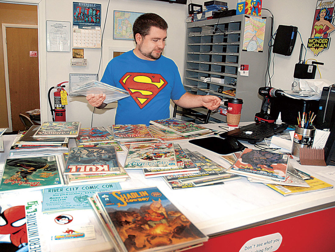 Photo by Evan Bevins Multiverse Comics owner Mick Williams sorts comic books at his store in the SouthGate Center on Pike Street in south Parkersburg. Williams said he loves older comics and will help customers track down issues they're seeking.