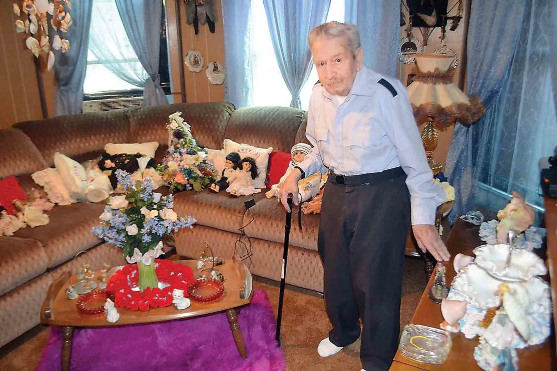 Joseph Littleton stands in the front room of his Muskingum Drive home in Marietta, where he has preserved his wife's favorite dolls, decorative plates, small statues and other art. (Photo by Michael Kelly)