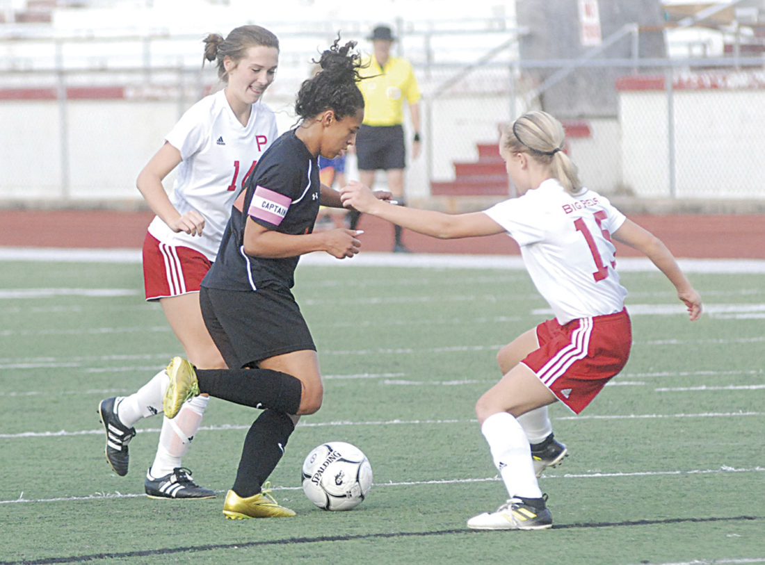 South Charleston's Makayla George gets converged on by Parkersburg's Sarah McDonnell, left, and Madison Spears. Spears scored four times and McDonnell once as the Big Reds defeated the Black Eagles, 5-1, Thursday night at Stadium Field. Photo by Jay W. Bennett.