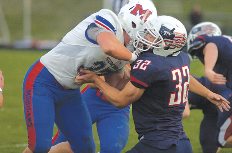 Parkersburg South's Tyee Gibson battles with Morgantown's Ben Turner during the Mohigans' 31-10 win over the Patriots Friday night at Erickson All-Sports Facility. Photo by Joe Albright.