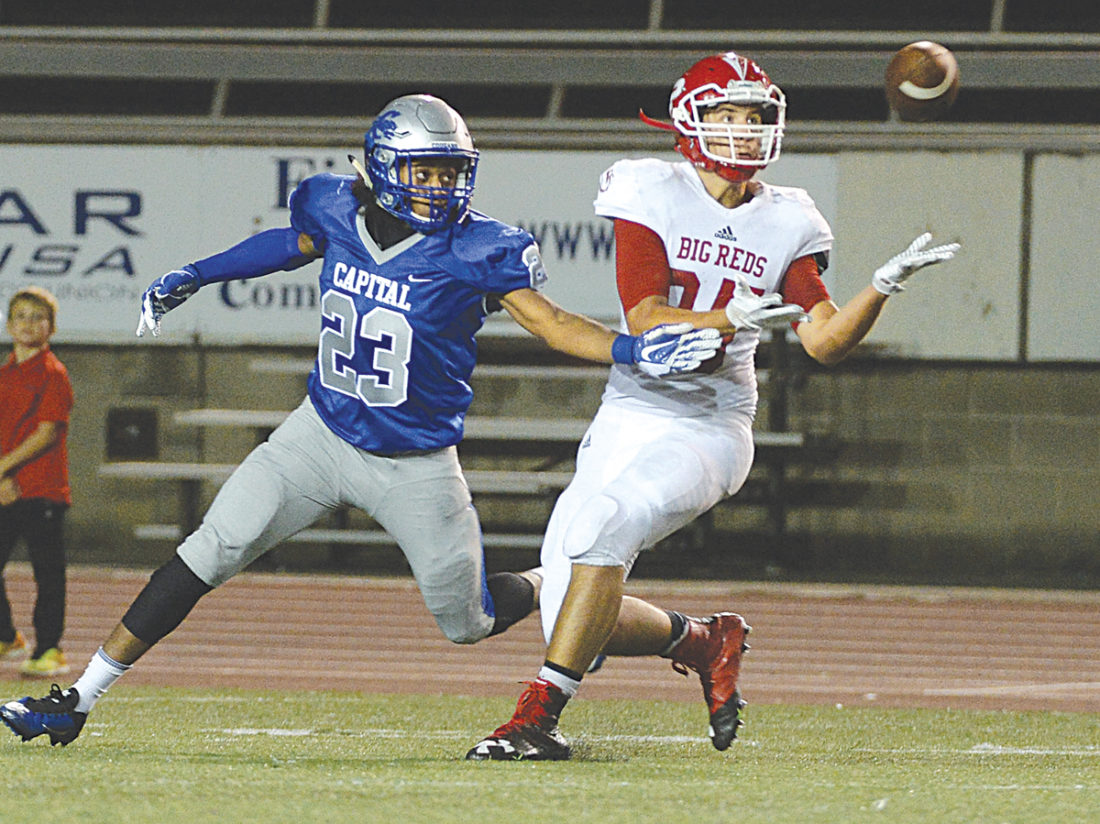 Parkersburg's Nathaniel Steed catches a pass from QB Jake Johnson as Capital's KJ Figures tries to tip it away. Photo by Chris Dorst, Charleston Gazette-Mail.